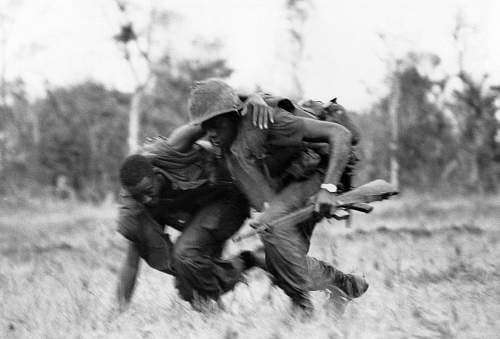 A marine helps his wounded comrade to cover despite North Vietnamese fire during battle on May 1.jpg