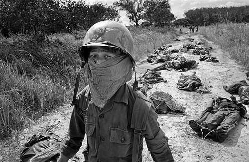 A Vietnamese litter bearer wears a face mask, Michelin rubber plantation, about 45 miles northea.jpg
