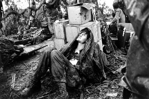 A wounded U.S. paratrooper grimaces in pain while waiting for medical evacuation at base camp in.jpg