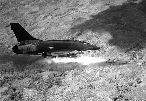 An Air Force F-100D Super Sabre aircraft fires a salvo of 2.75-inch rockets against an enemy pos.jpg