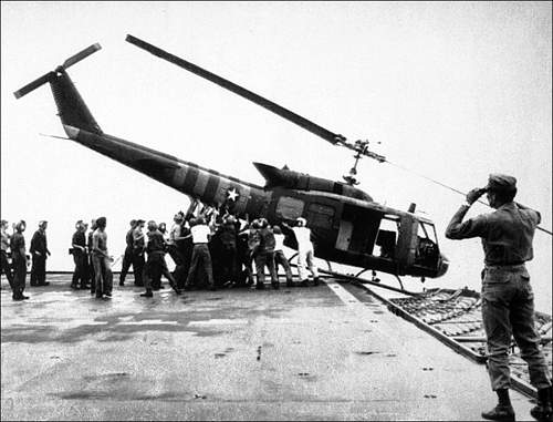 April 29, 1975, U.S. Navy personnel aboard the USS Blue Ridge push a helicopter into the sea off.jpg