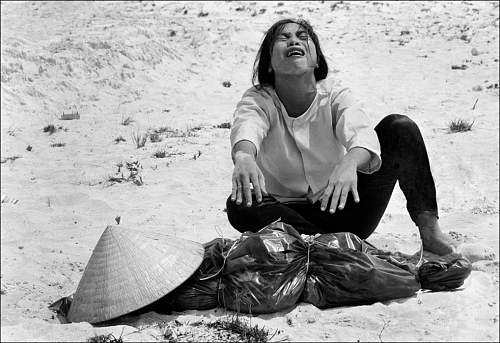 April 1969, a South Vietnamese woman mourns over the body of her husband, found with 47 others i.jpg