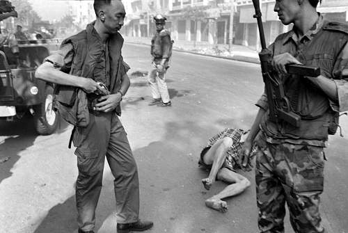 South Vietnamese General Nguyen Ngoc Loan holsters his gun after executing suspected Viet Cong o.jpg