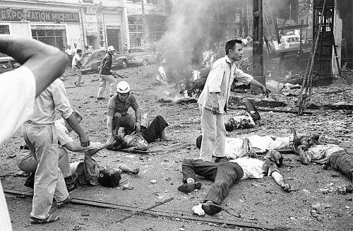 Injured Vietnamese receive aid as they lie on the street after a bomb explosion outside the U.S..jpg