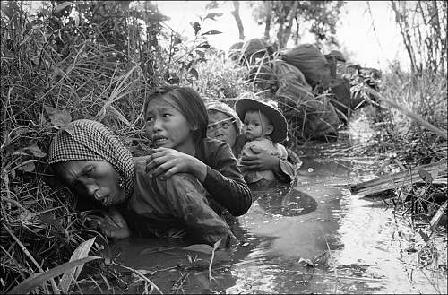 Jan. 1, 1966, women and children crouch in a muddy canal as they take cover from intense Viet Co.jpg