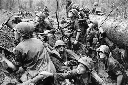 June 15, 1967, American infantrymen crowd into a mud-filled bomb crater and look up at tall jung.jpg