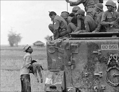 March 19, 1964, a father holds the body of his child as South Vietnamese Army Rangers look down .jpg