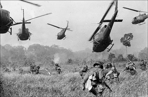 March 1965, hovering U.S. Army helicopters pour machine gun fire into a tree line to cover the a.jpg