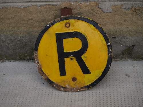 round plaque with black R on yellow background