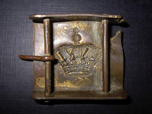 Romanian army belt buckle , with shrapnel damage . Eastern front