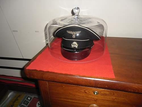 Glass dome to protect black SS visor hat on display