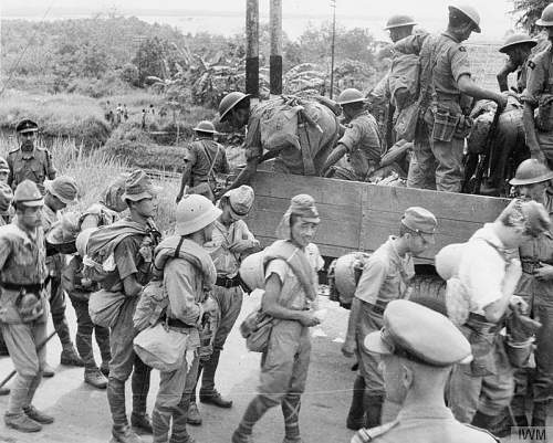 Click image for larger version.  Name:Disarmed Japanese soldiers leave the city of Singapore for prisoner of war camps as men of the 5.jpg Views:625 Size:91.3 KB ID:833635