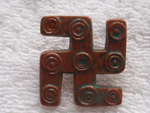 Brown plastic swastika with a series of circles in the arms