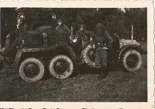 SS men in camo smocks/bug net on truck.