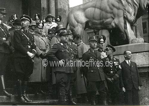 Himmler and Wolff in grey overcoat with black collar and black cap....
