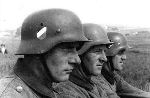 Nice period shot of 3 M35 Heer double decal helmets in use....